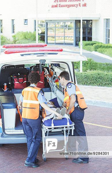 Rettungssanitäter  die Patienten aus dem Krankenwagen fahren
