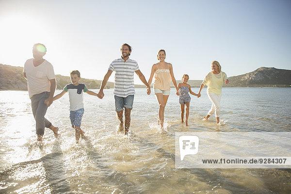 Familienwanderung im flachen Wasser am Strand