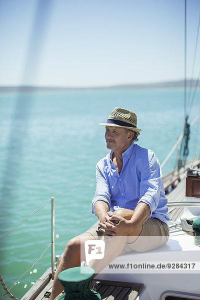 Älterer Mann auf dem Boot im Freien sitzend