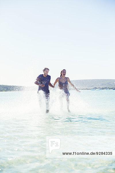 Pärchenspritzen im Wasser am Strand