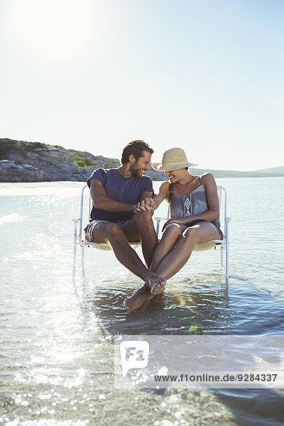 Paar auf Stühlen in Wellen sitzend
