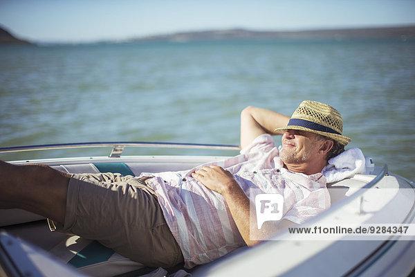 Älterer Mann entspannt im Boot auf dem Wasser