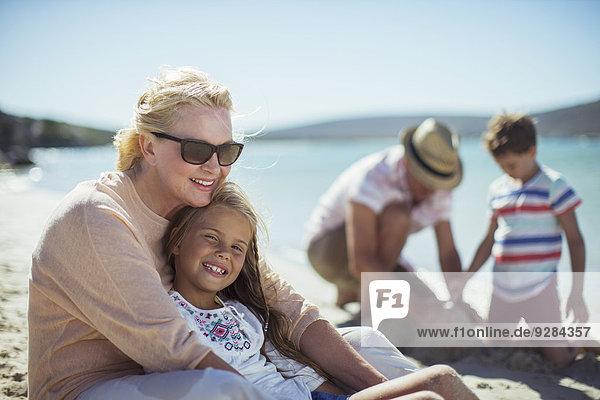Großmutter umarmt Enkelin am Strand