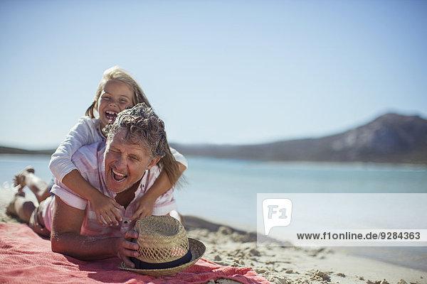 Großvater und Enkelin beim Spielen am Strand, Großvater und Enkelin beim Spielen am Strand