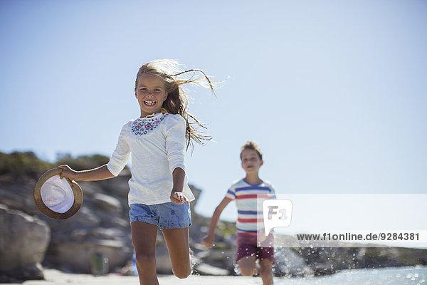 Junges Mädchen und Junge laufen am Strand entlang