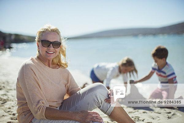 Ältere Frau am Strand sitzend mit Familie