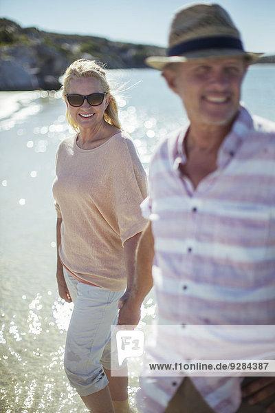 Ein Paar  das zusammen im Wasser spazieren geht.
