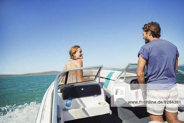 Mann steuert Boot mit Freundin