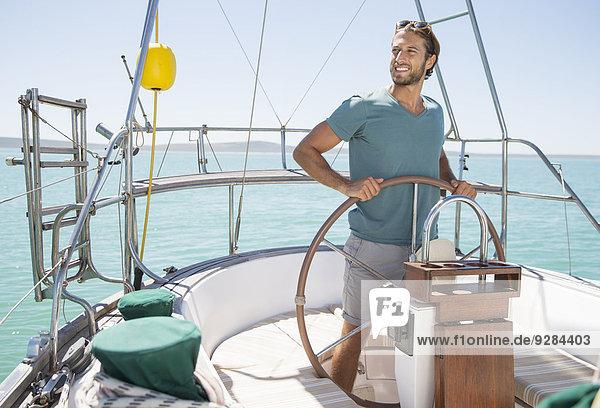 Mann steuert Segelboot auf dem Wasser