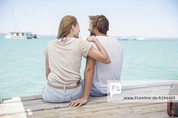Paar sitzt auf dem Rand des Holzdocks zusammen