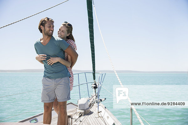 Paarumarmung an Deck eines Segelbootes