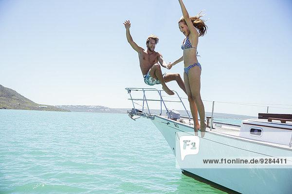 Paare  die zusammen vom Boot springen.