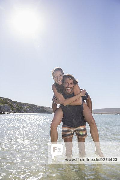 Frau wird vom Freund in Wellen zurück getragen