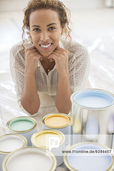 Woman sitting in front of paint cans