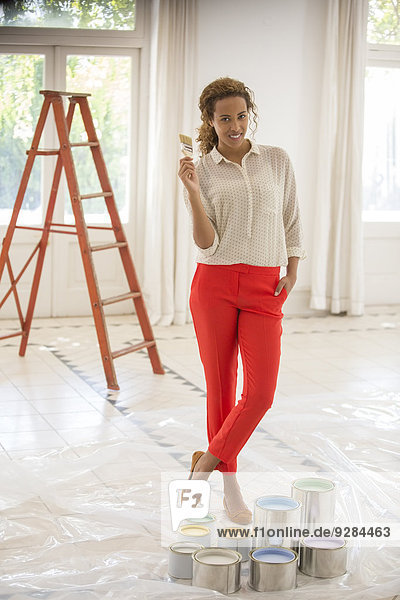 Woman holding paintbrush near paint cans