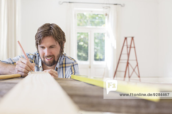 Man marking wood in living area