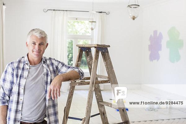 Older man smiling near ladder in livingroom