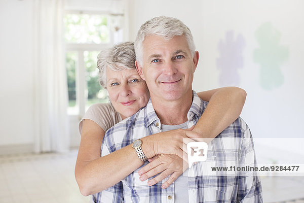 Older couple hugging in living space