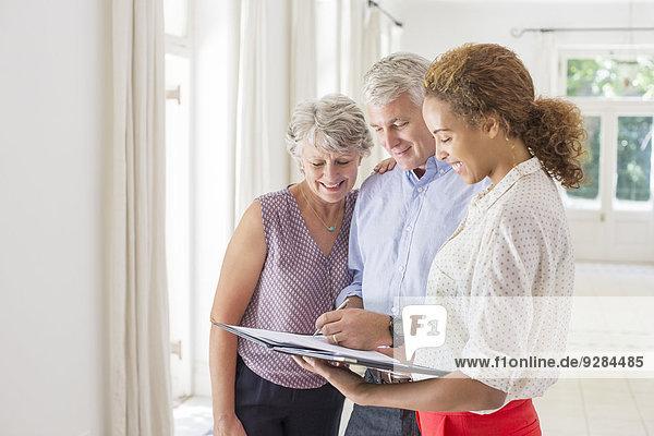 Ältere Paare und Frauen unterzeichnen Dokumente