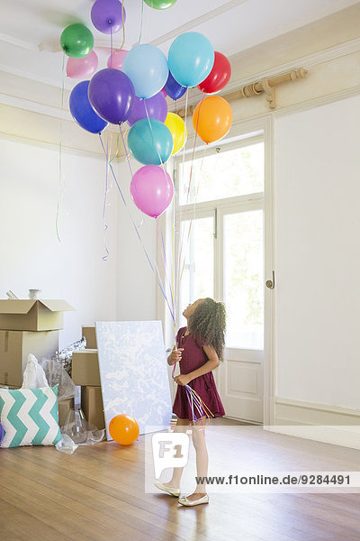 Young girl holding balloons in living space