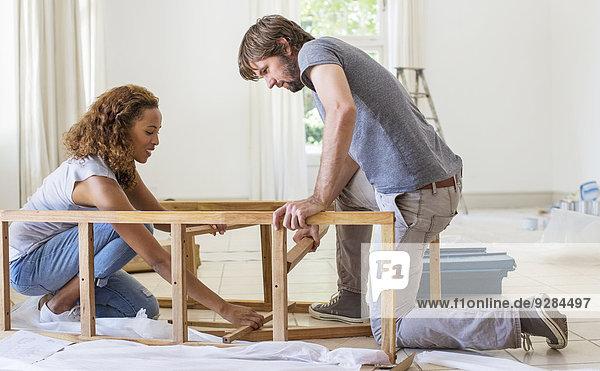 Couple building furniture together