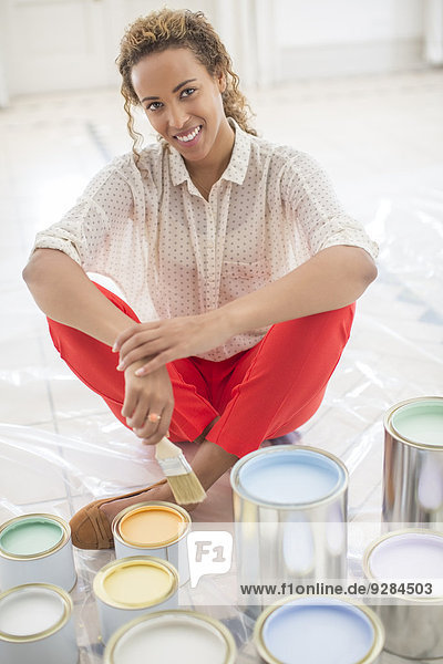 Woman overlooking space with paint cans near