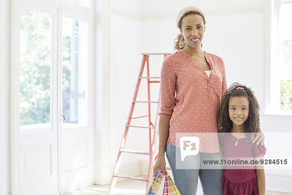 Mother and daughter smiling in living space