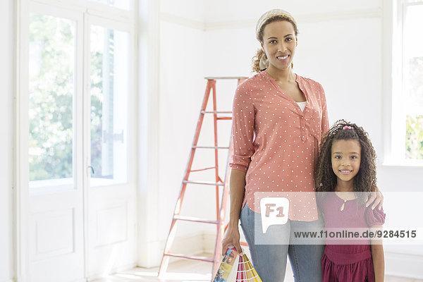 Mutter und Tochter lächeln im Wohnraum