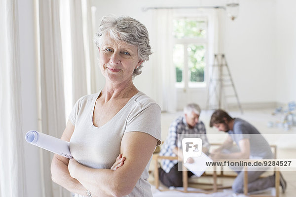 Older woman holding construction plans