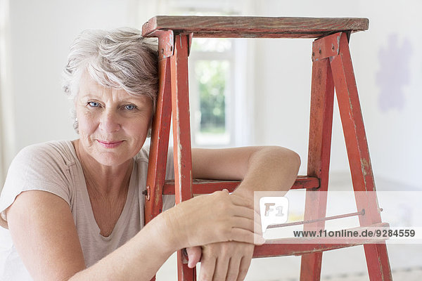 Older woman leaning on ladder in living space