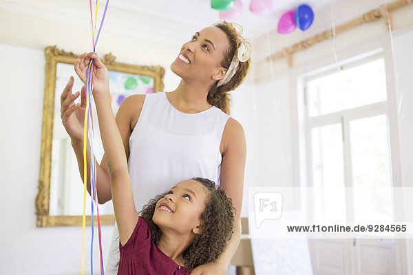 Mother and daughter holding balloons together