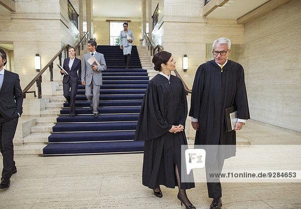 Richter und Anwälte gehen durch das Gerichtsgebäude.