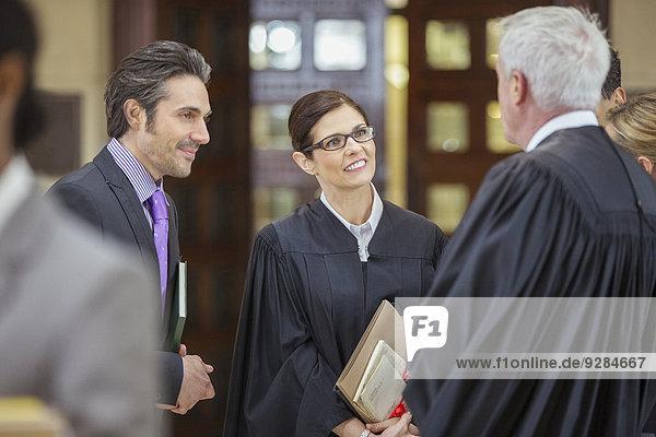 Richter und Anwälte im Gespräch außerhalb des Gerichtssaals