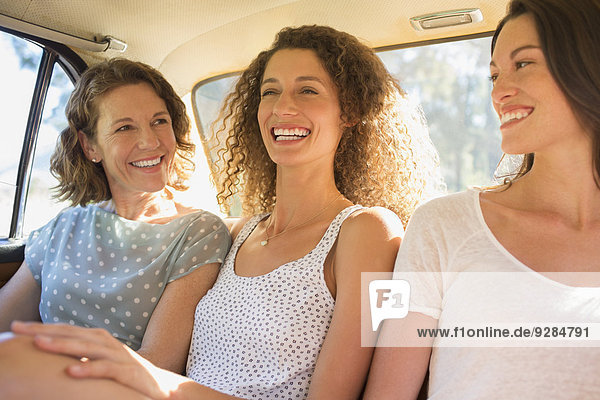 Drei Frauen  die zusammen auf dem Rücksitz sitzen.