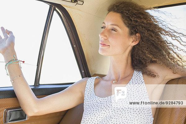 Frau fühlt sich wie eine Brise aus dem Fenster des Rücksitzes