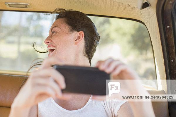 Frau auf dem Rücksitz fotografiert mit dem Handy