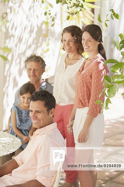 Familie um den Tisch im Freien versammelt
