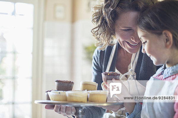 Großmutter bietet Enkelin Muffins an