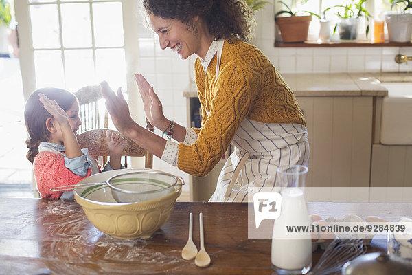 Mutter und Tochter hoch fünf in der Küche