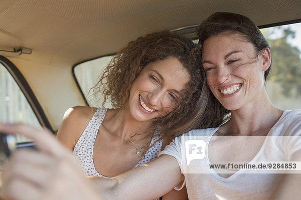Schwestern beim gemeinsamen Fotografieren auf dem Handy