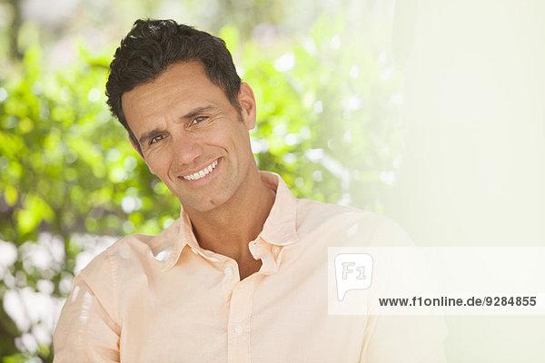 Mann lächelt im Freien