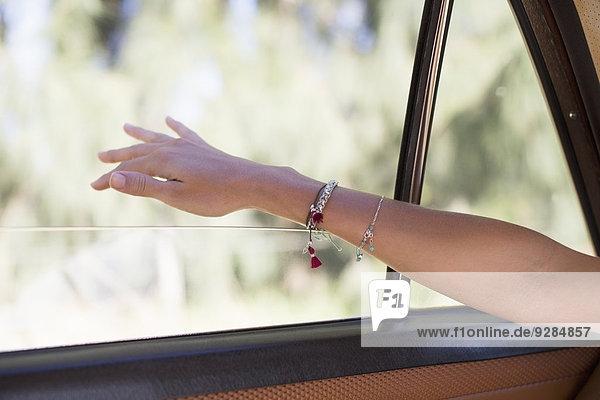 Frau spürt Wind auf der Hand durch das Autofenster