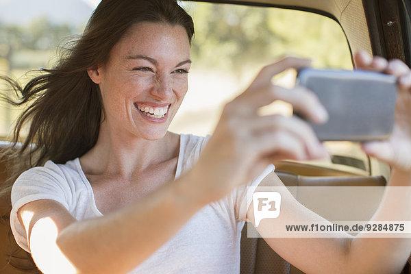 Frau im Auto beim Fotografieren mit dem Handy
