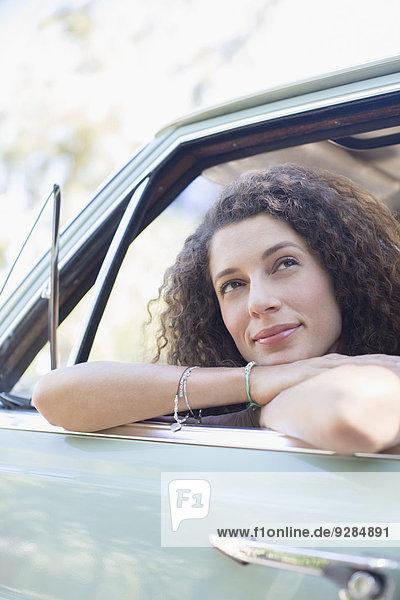 Frau entspannt an der Autotür während der Autofahrt