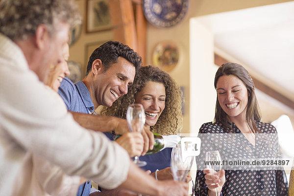 Mann schüttet Getränke an Familienmitglieder aus
