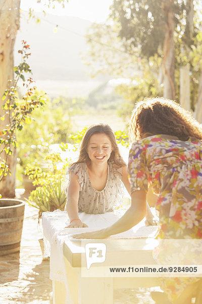 Mutter und Tochter legen Tischdecke auf den Tisch