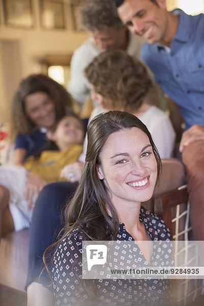Frau lächelt im Wohnraum mit Familie