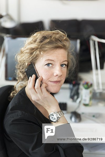 Woman in office talking via cell phone