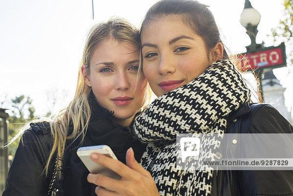 Junge Frauen im Freien schauen gemeinsam aufs Handy