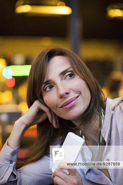 Frau zufrieden mit guten Nachrichten auf dem Smartphone unterwegs